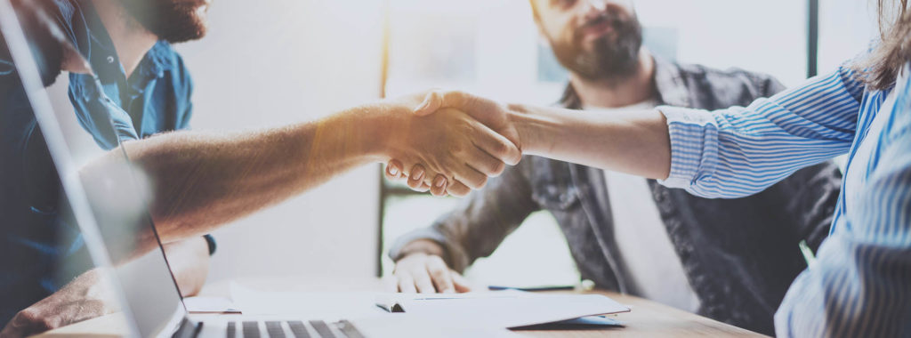 how to ask for sponsorship - Business partnership handshake concept.Photo two coworkers handshaking process.Successful deal after great meeting.Horizontal, blurred background.Wide.